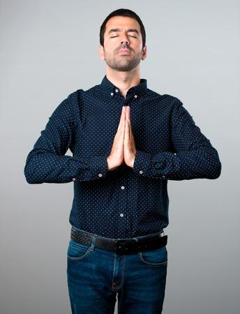 Handsome man pleading on grey background Stock Photo