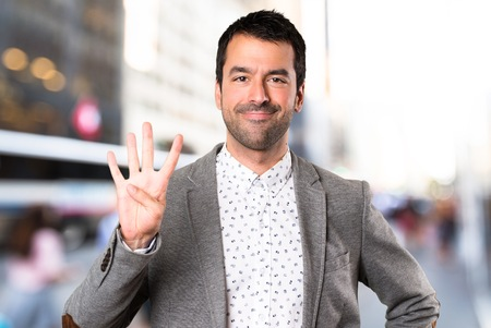 Handsome man counting four on unfocused background Stock Photo