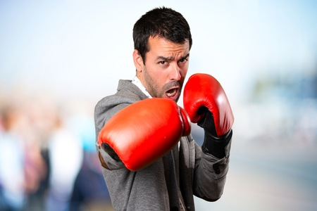 Handsome man with boxing gloves on unfocused background Stock Photo