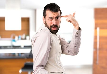 Handsome man with vest making crazy gesture inside house