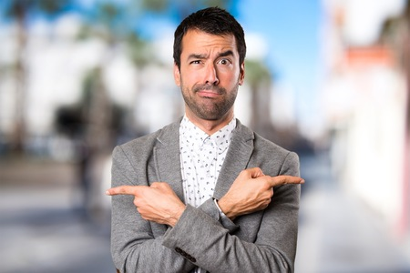 Handsome man pointing to the laterals having doubts on unfocused background Stock Photo