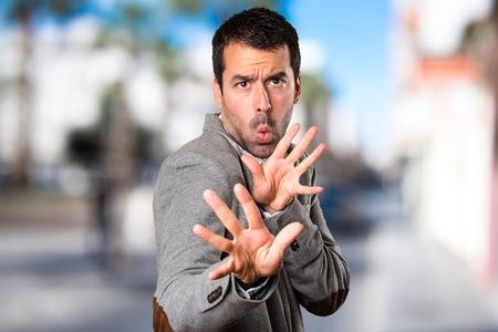 Handsome man making NO gesture on unfocused background