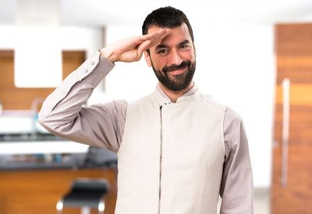 Handsome man with vest saluting inside house