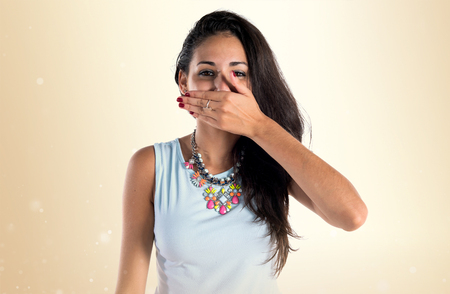 Young cute girl covering her mouth on ocher background Stock Photo