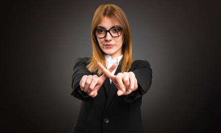 Young business woman making NO gesture on dark background Фото со стока