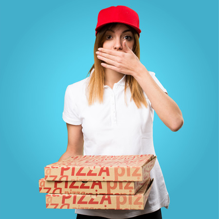Pizza delivery woman covering her mouth on colorful background Stock Photo