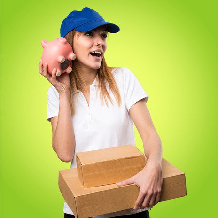 Surprised Delivery woman holding a piggybank on colorful background Stock Photo