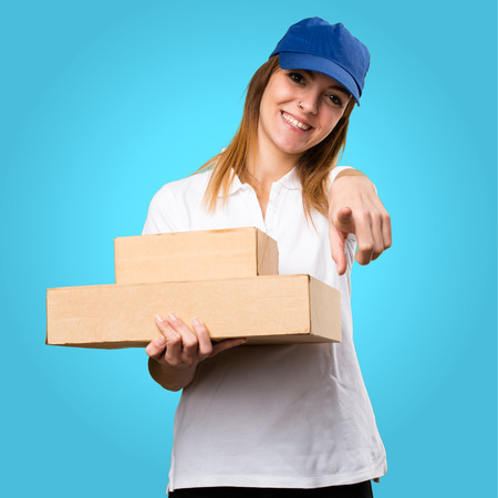 Delivery woman pointing to the front on colorful background
