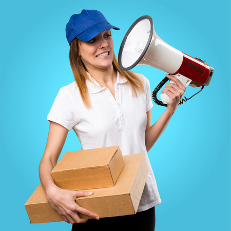 Surprised Delivery woman holding a megaphone on colorful background Stock Photo
