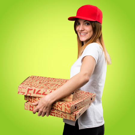 Happy pizza delivery woman on colorful background Stock Photo