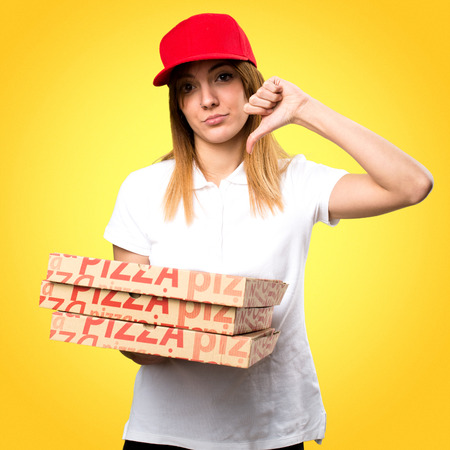 Pizza delivery woman making bad signal on colorful background Stock Photo
