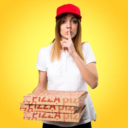 Pizza delivery woman making silence gesture on colorful background Stock Photo