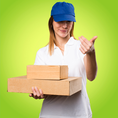 Delivery woman doing coming gesture on colorful background Stock Photo