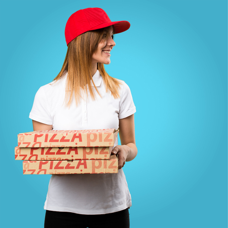 Pizza delivery woman looking lateral on colorful background Stock Photo