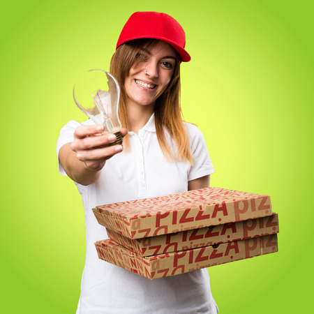 Pizza delivery woman holding a bulb on colorful background