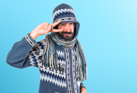 Man with winter clothes dancing on colorful background