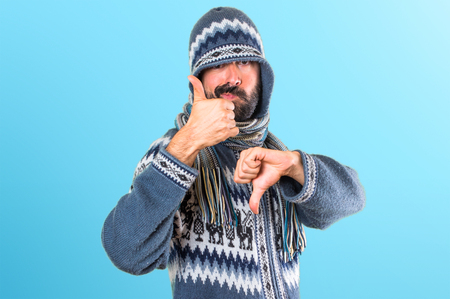 Man with winter clothes making good-bad sign on colorful background