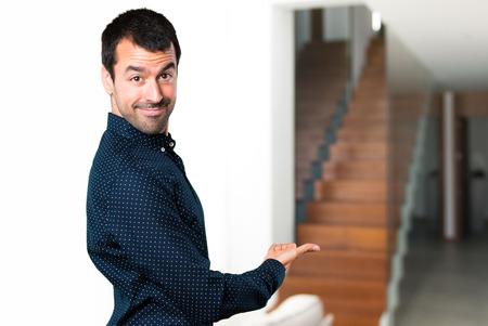 Handsome man presenting something inside house