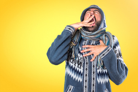 Man with winter clothes yawning on colorful background Stock Photo
