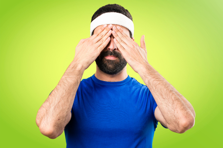 Funny sportsman covering his eyes on colorful background