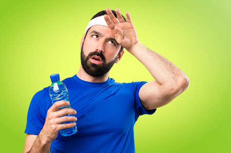 Funny sportsman with a bottle of water on colorful background Фото со стока