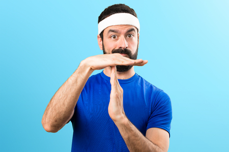 Funny sportsman making time out gesture on colorful background