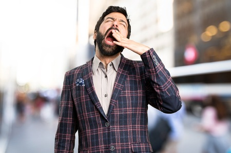 Well dressed man yawning in the city