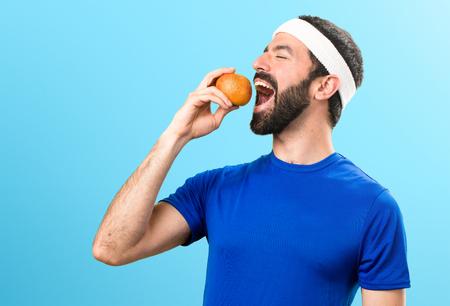 Funny sportsman holding an orange juice on colorful background