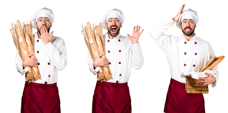 Young baker holding some bread and making surprise gesture