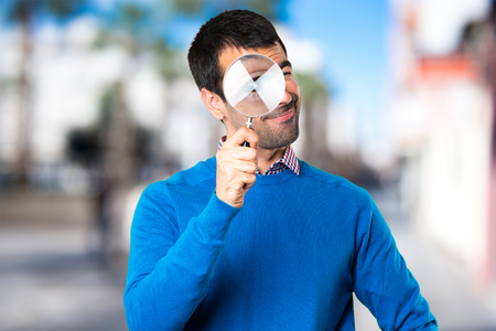 Handsome young man with magnifying glass on unfocused background