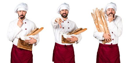 Young baker holding some bread and making bad signal Stock Photo