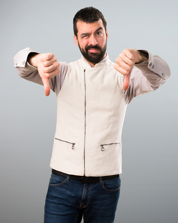 Handsome man with vest making bad signal on grey background