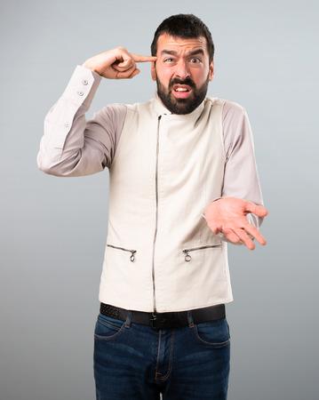 Handsome man with vest making crazy gesture on grey background