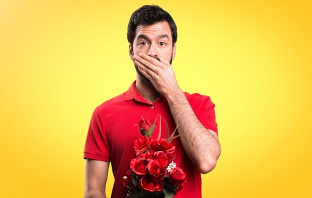 Handsome man holding flowers covering his mouth on yellow background Stock Photo