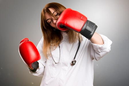 Young doctor woman with boxing gloves on grey background