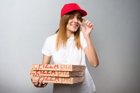 Pizza delivery woman making tiny sign on textured background