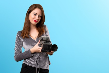Beautiful young girl filming on colorful background