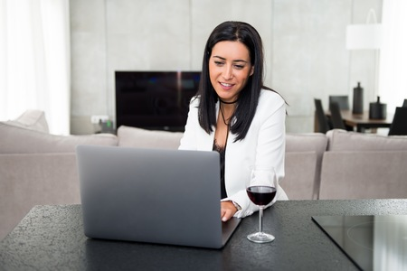 Beautiful young girl with a laptop and a wine glass Imagens