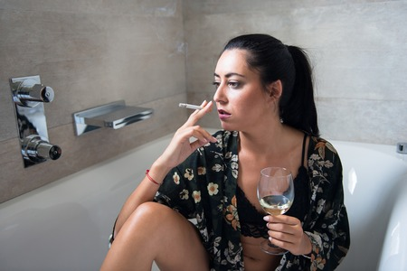 Beautiful girl in the bathroom with a wine glass