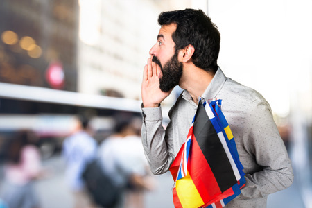 Handsome man with beard holding many flags and shouting Stock Photo