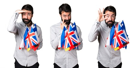 Handsome man with beard holding many flags and showing something