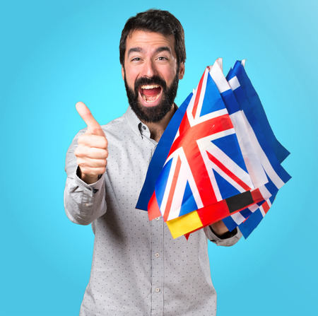 Handsome man with beard holding many flags and with thumb up Stock Photo