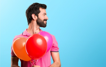 Handsome young man holding balloons and  looking lateral on colorful background Stock Photo
