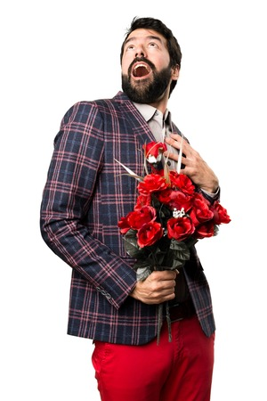 Surprised Well dressed man holding flowers on white background