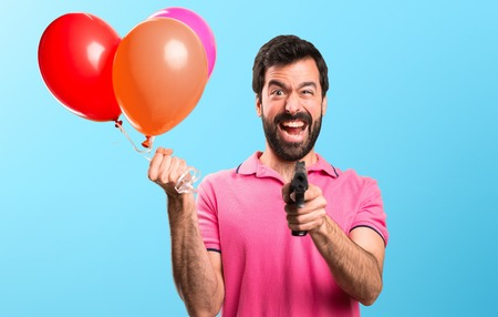 Handsome young man holding balloons and  holding a pistol on colorful background Stock Photo