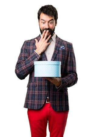 Well dressed man holding a gift on white background