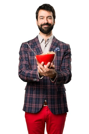 Happy Well dressed man holding a bowl of cereals on white background