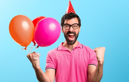 Lucky handsome young man holding balloons on colorful background