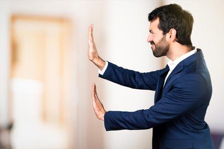 Man pushing something on unfocused background