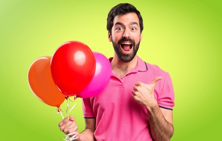 Handsome young man holding balloons and  with thumb up on colorful background